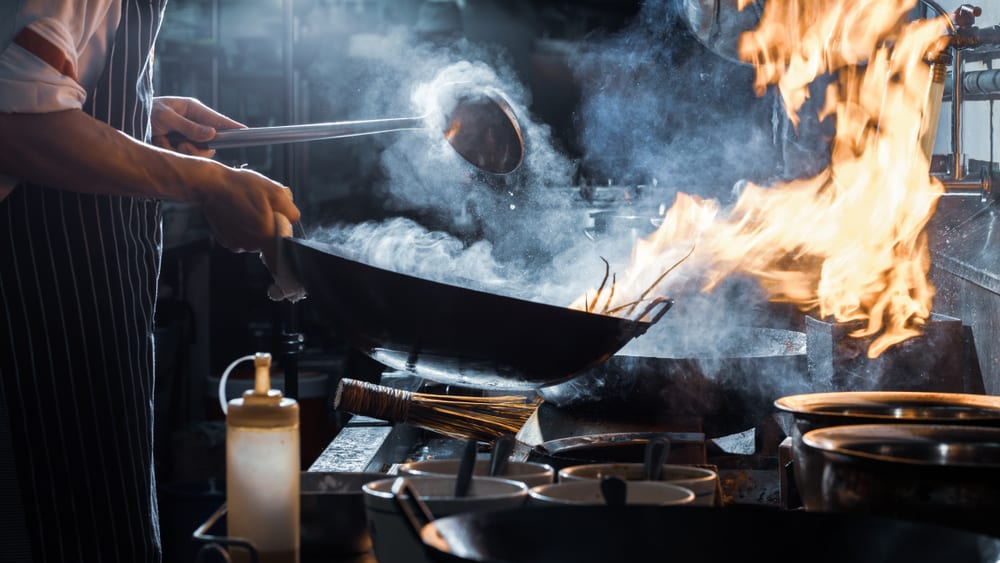 frying pan with fire in restaurant kitchen